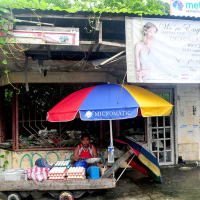 street corner egg vendor in front of abandoned structure under an umbrella
