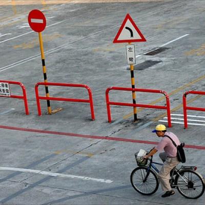 man biking by in a yellow cap