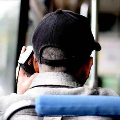 old man on bus listening to a portable radio
