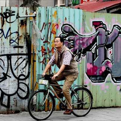 man riding a bike in front of a wall covered in graffiti