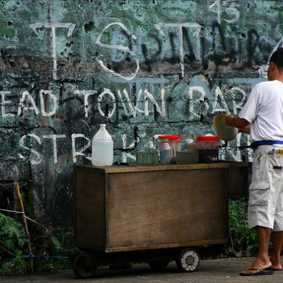 food cart in front of a graffiti covered wall