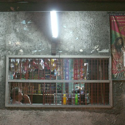 sari sari store with a fluorescent tube right above the barred windows