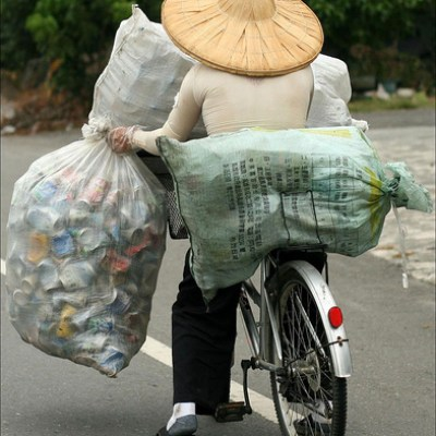 farmer carrying sacks of empty cans on a bike