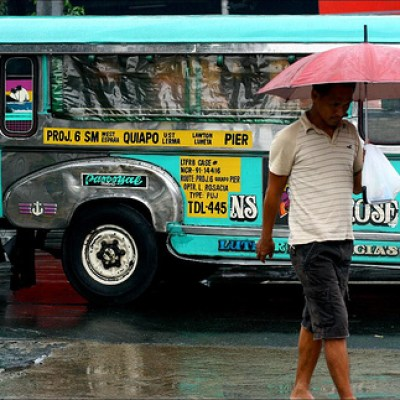 man with an umbrella in front of a jeepney on a rainy day