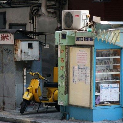 yellow Vespa on a street corner