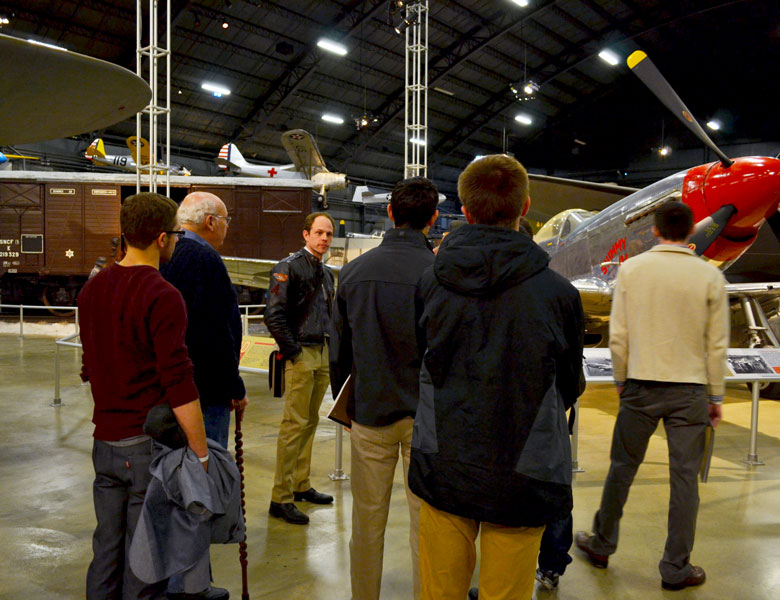 Team members circle around as Jim Barfield discusses the history of the planes in the museum.