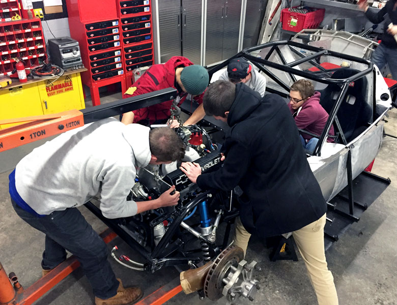 The team lowers the engine into the car.