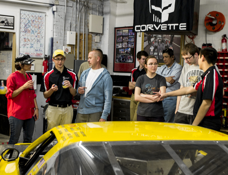 Team members and their families gather around the car during the Genius Garage Open House.