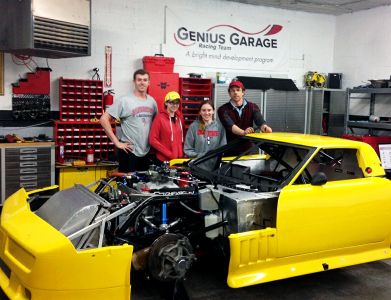 Maxwell Everett, Taylor Wilson, Isabelle Beecy, and Casey Putsch pose by the newly assembled and freshly painted yellow Corvette.
