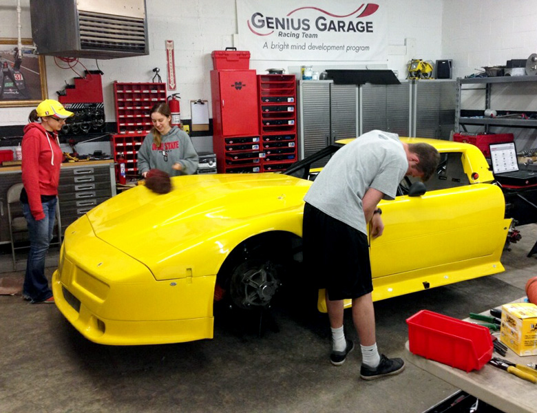 Max Everett works on the car while Taylor Wilson and Isabelle Beecy discuss PR and website strategy.