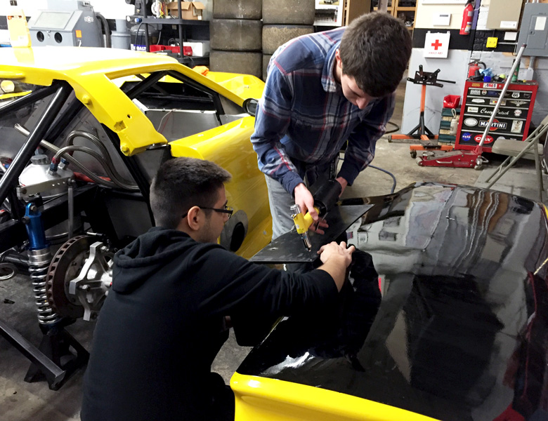 Federico Aponte and Chris Scherzer work on riveting parts of the car together.