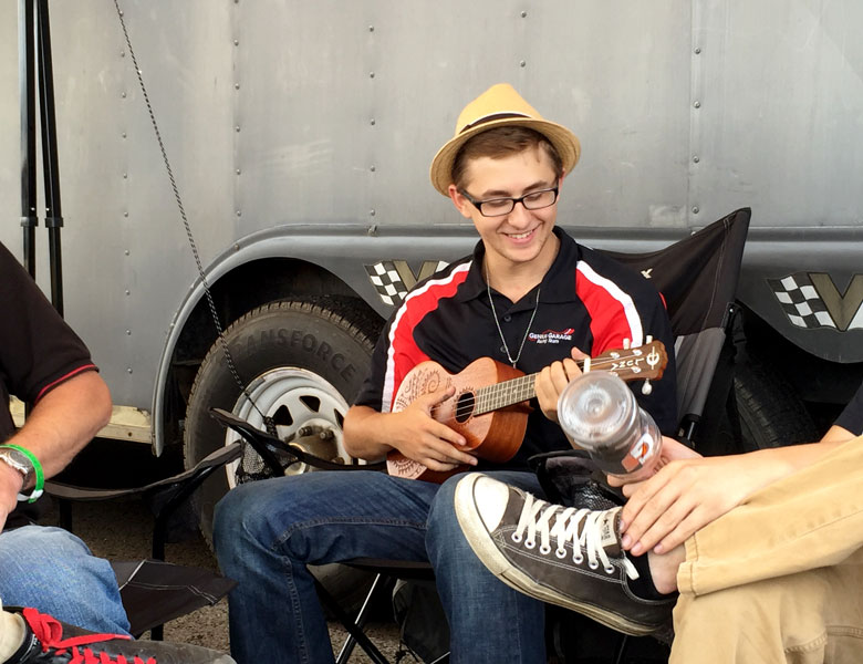 Zach Sroka plays Clint's ukelele for the team and spectators passing by the pits.