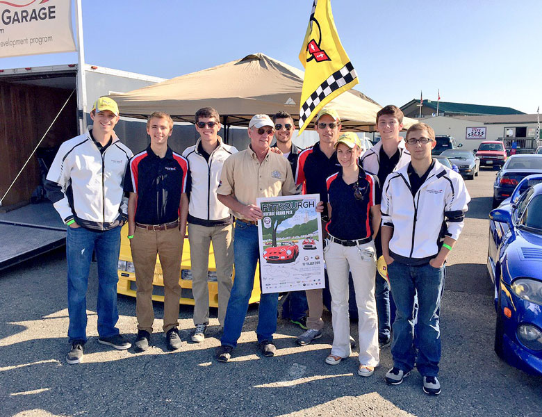 Max, Clint, Chris, Nathan, Casey, Taylor, Dan, and Zach give an autographed poster to Chuck at Central Classic Cars to thank them for their support!