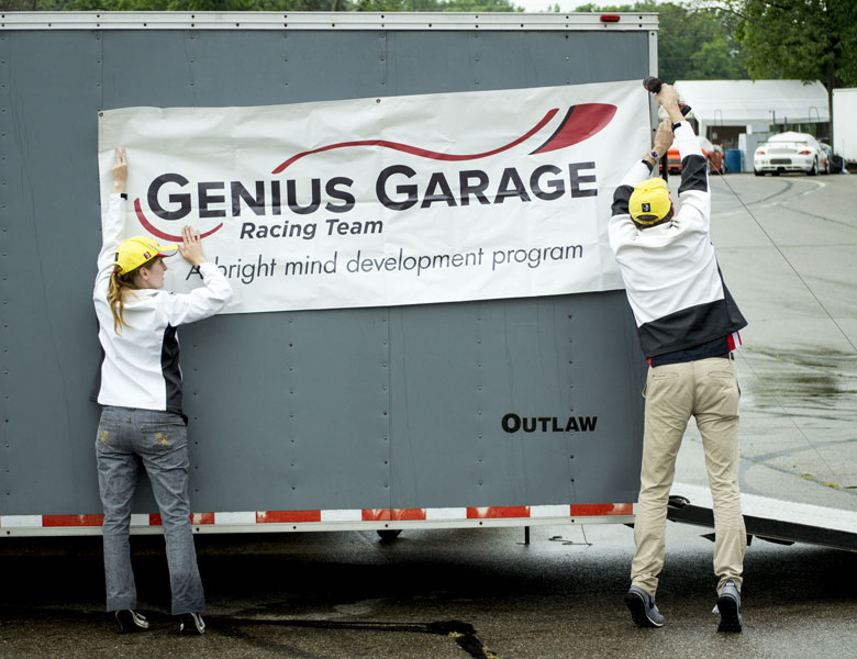 Izzy and Casey hang up the Genius Garage banner so friends and family could find our set up site.
