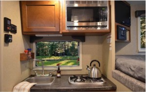 The kitchen has a microwave and two burner stove top with flush mounted tempered glass top for added counter space.