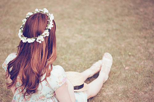 草原に座って景色を見ている双子の女の子たちのフリー写真素材(商用可)