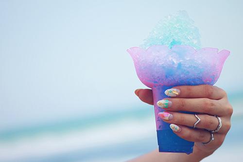 海で食べるブルーハワイのかき氷のフリー写真素材(商用可)