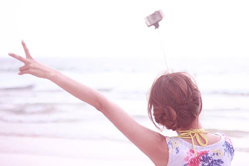 自撮り棒で撮影している女の子のフリー写真素材(商用可)