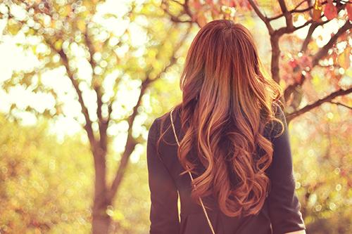 美しい紅葉たちに囲まれて癒やされている女の子のフリー写真素材(商用可)