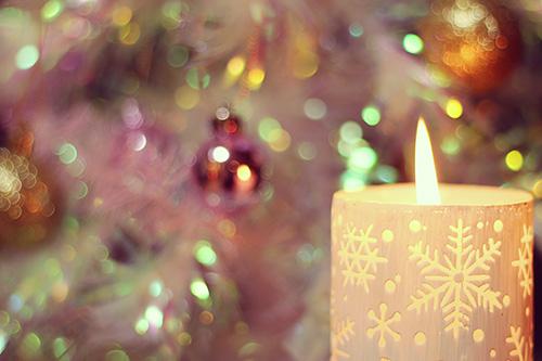 クリスマスツリーの前で灯る雪の結晶柄のキャンドルのフリー写真素材(商用可)