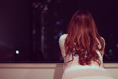 寝る前にひとり夜景を眺める女の子のフリー写真素材(商用可)