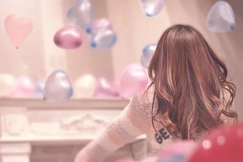 ゆめかわいいハートの風船でふわふわ遊ぶ女の子のフリー写真素材(商用可)