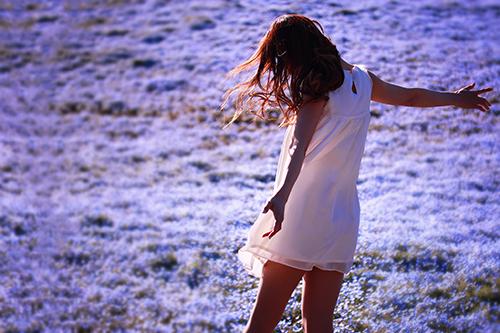 ネモフィラの花畑で全身に春の風を浴びている女の子のフリー写真素材(商用可)