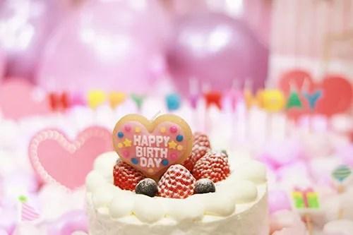 オシャレな誕生日画像:ケーキに刺さった可愛いハートのバースデーキャンドルのフリー写真素材(商用可)