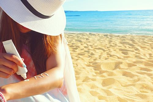 炎天下のビーチで日焼け止めを塗る女の子のフリー写真素材(商用可)