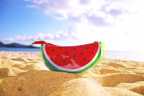 ビーチに置かれたスイカのポーチのフリー写真素材(商用可)