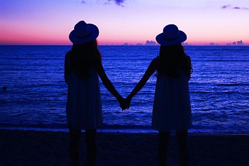 夕陽が沈みきった海で手をつなぐ双子の女の子たちのフリー写真素材(商用可)