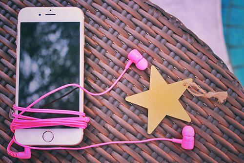 音楽好き女子の必需品☆iPhoneとピンクのイヤホンのフリー写真素材(商用可)
