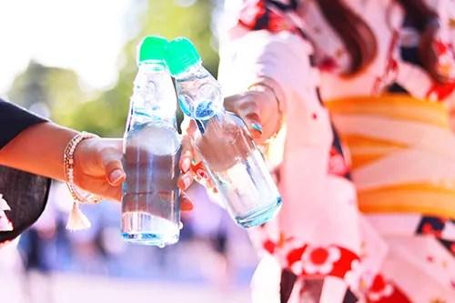 お祭りで買ったラムネで乾杯する浴衣の女の子たちのフリー写真素材(商用可)