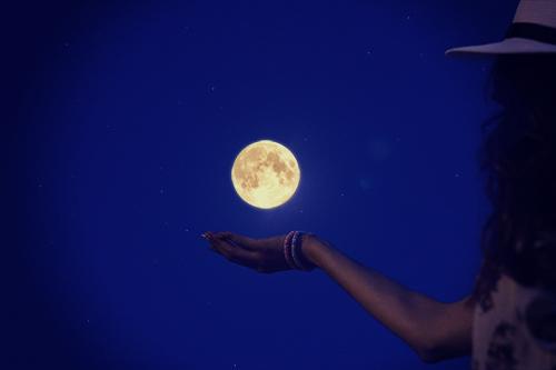 十五夜の満月に手をかざす神秘的な女の子のフリー写真素材(商用可)