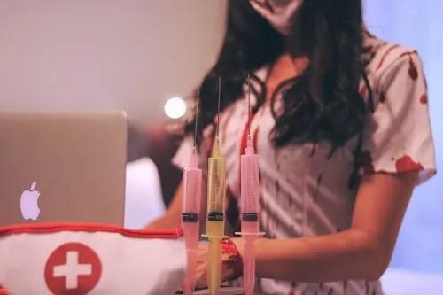 次の採血者をパソコンで管理する血まみれナースな女の子のフリー写真素材(商用可)