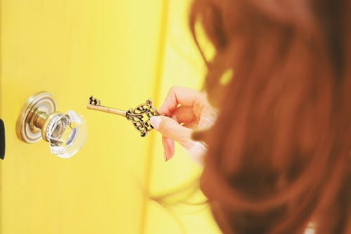 ドアの前で鍵穴を探している女の子のフリー写真素材(商用可)