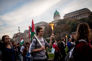 Backdropped by the Royal Palace in the Castle of Buda, young people hold torches and wave national flags as they march through the streets of Budapest to re-enact the protest march of Hungarian students in 1956, which ignited the revolution and war of independence against communist rule and the Soviet Union, Tuesday, Oct. 22, 2013, the eve of the 57th anniversary of the outbreak of the 1956 revolution. Photo Credit: AP Photo/MTI, Balazs Mohai