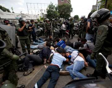 Bolivarian National Guardsmen surround a group of anti-government demonstrators, detained during a protest in Caracas, Venezuela, May 14, 2014.  (AP Photo/Fernando Llano)