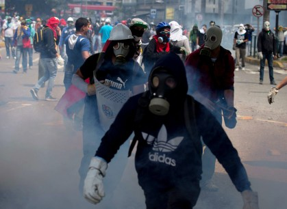 Masked anti-government demonstrators walk amid teargas fired by Bolivarian National Police during a protest to demand the release of arrested student protesters in Caracas, Venezuela,  May 12, 2014.  (AP Photo/Fernando Llano)