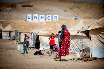 A refugee family in front of her tent with the UNHCR letters on barrels in the background, Sept. 3, 2013. (Copyright Flo Smith/NurPhoto/NurPhoto/Corbis / APImages)