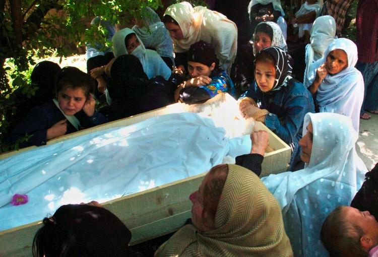 Relatives sit besides the coffin containing body of Zakia Zaki, June 6, 2007. Photo credit: Ali Shah Paktiawal, EPA/SYED JAN SABAWOON