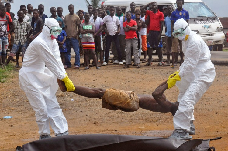 Health workers places the body of a man, inside a plastic body bag as he is suspected of dying due to the Ebola virus as people, rear, look on in Monrovia, Liberia, Thursday, Sept. 4, 2014. Photo credit: AP Photo/Abbas Dulleh