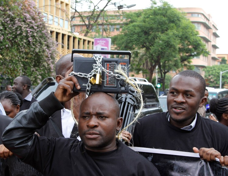 Kenyan journalists display a symbolically locked radio, during a protest against the Media Bill in Nairobi, Kenya, Tuesday, Dec. 3, 2013. A media protest was called on by various media houses to protest new draconian laws that are being tabled by parliament. Photo credit: AP Photo/Khalil Senosi