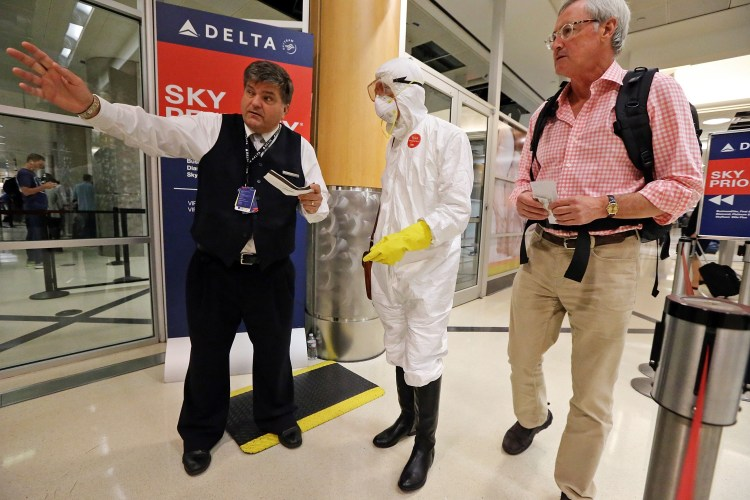 Two days after a man in Texas was diagnosed with Ebola, Dr. Gil Mobley, a Missouri doctor, checks in to board a plane dressed in full protection gear Thursday morning, Oct. 2, 2014, at Hartsfield-Jackson Atlanta International Airport. He was protesting what he called mismanagement of the crisis by the federal Centers for Disease Control and Prevention. Photo credit: AP Photo/Atlanta Journal-Constitution, John Spink) MARIETTA DAILY OUT; GWINNETT DAILY POST OUT; LOCAL TELEVISION OUT; WXIA-TV OUT; WGCL-TV OUT
