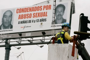 "A city worker fixes a traffic light near a banner portraying two men imprisoned for having sexually abused minors, in Bogota, Wednesday, Sept. 26, 2007. The banner reads in Spanish ""Condemned for sexually abusing girls of 4 and 13 years."" Photo credit: AP Photo/Fernando Vergara"