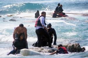 A man rescues an migrant from the Aegean sea, in the eastern island of Rhodes, April 20, 2015. (Argiris Mantikos/Eurokinissi via AP)