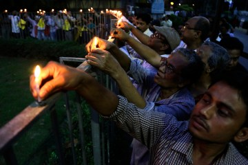 Intellectuals and people in general put candle lights on a fencing during a silent protest rally against the killing of writer and blogger Abhijit Roy of Bangladesh origin, in Kolkata, India, March 1, 2015. Roy was stabbed to death by religious fundamentalists in Dhaka, Bangladesh on Feb. 26 while returning from a book fair with his wife. The procession was organised by Bangla Bhasa O Chetana Samiti. (AP Photo/ Bikas Das)