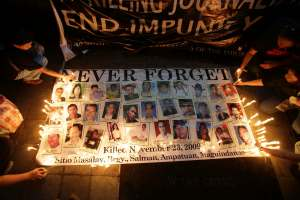 Filipinos light candles on a slogan bearing images of victims of a massacre that killed 58 people, including 32 journalists, as they mark it's 5th anniversary with a candle lighting event at the historic EDSA Shrine in suburban Quezon city, north of Manila, Philippines on Sunday, Nov. 23, 2014.Five years after gunmen flagged down a convoy of cars and massacred all 58 occupants, including scores of journalists, in Maguindanao southern Philippine province, the body count continues to rise. The Ampatuan clan is tagged as the prime suspects in the carnage. (AP Photo/Aaron Favila)