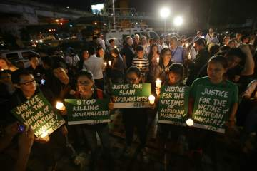 Filipinos hold slogans during a candle lighting event to mark the 5th anniversary of the massacre of 58 people, 32 of them journalists, in suburban Quezon city, north of Manila, Philippines on Sunday, Nov. 23, 2014. Five years after gunmen flagged down a convoy of cars and massacred the occupants, in Maguindanao, southern Philippine province, the body count continues to rise. The Ampatuan clan is tagged as the prime suspects in the carnage. (AP Photo/Aaron Favila)