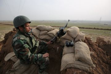 A Kurdish Peshmerga soldier stands guard, overlooking the road between Mosul and Tal Afar, Iraq, Jan. 27, 2015. (AP Photo/Bram Janssen, File)